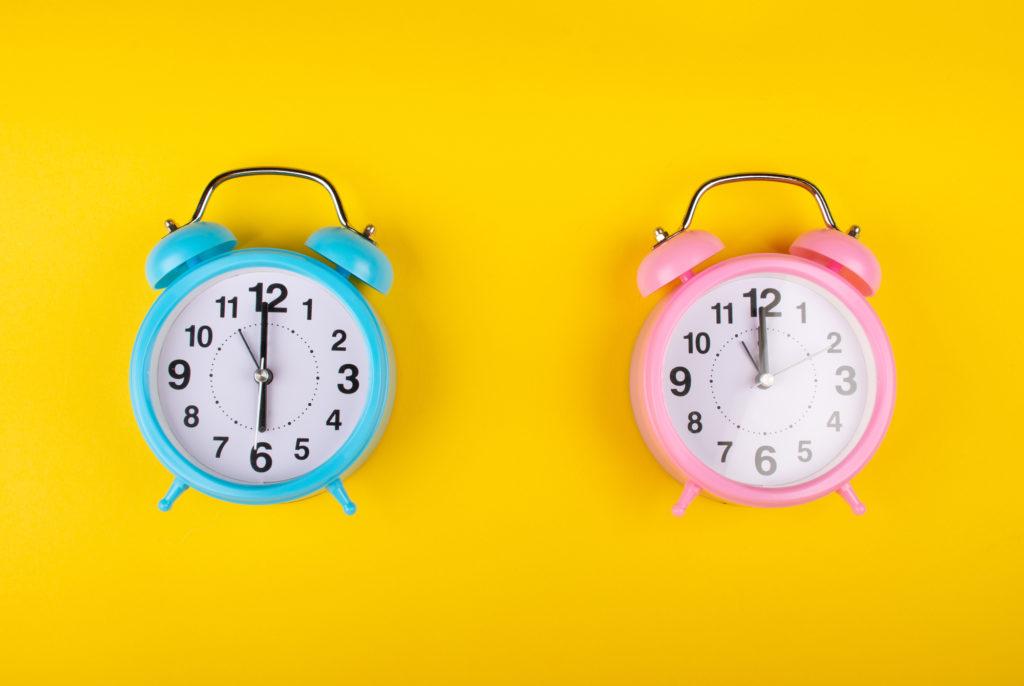 Deux réveils sur un fond jaune vif montrant l'heure différente que le concept d'une personne du matin et une chouette de nuit